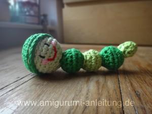Amigurumi-Raupe aus grüner Baumwolle.