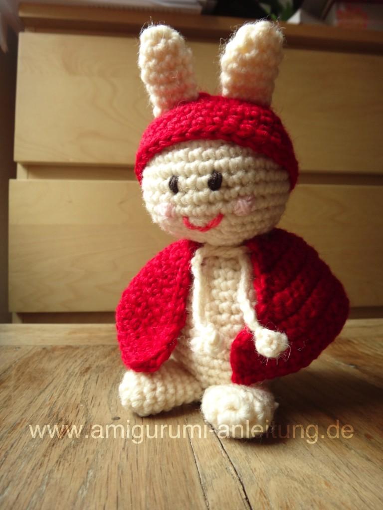 Der Amigurumi-Hase hat einen Mantel und eine rote Mütze.